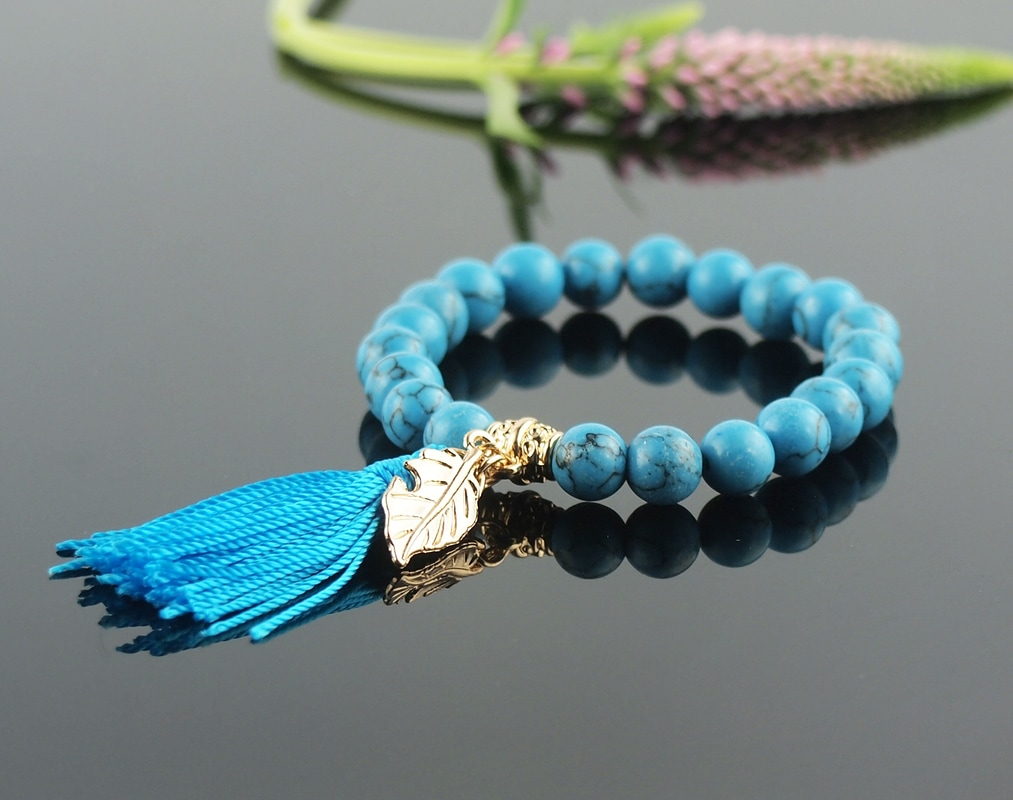 Deep marine blue turquoise beads have black matrix in this attractive stretch bracelet with blue silk tassel and golden leaf charm accent.
